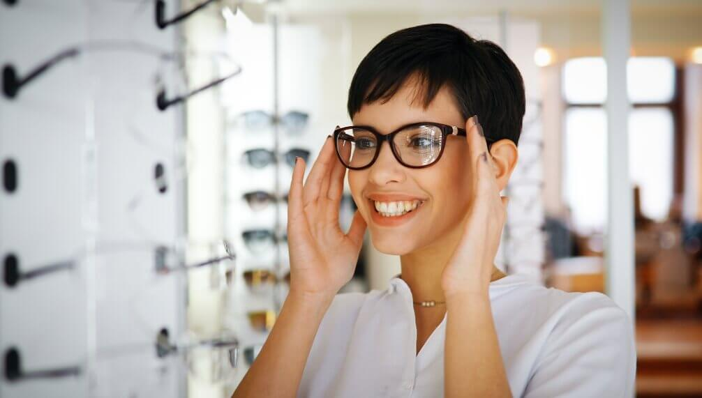 woman smiling about the glasses she just tried on