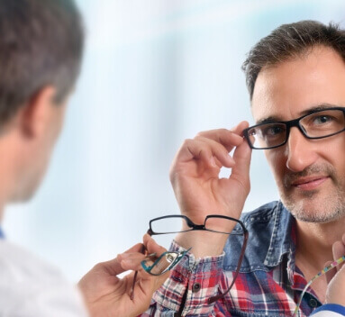 guy trying out different glasses frames