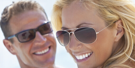 man and woman smiling with sunglasses on