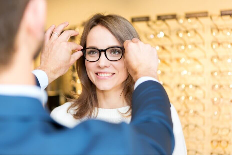woman having a man help her fit her frames